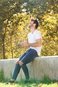 Volledige lichaam vrolijke man zittend op muur in park met cellphone