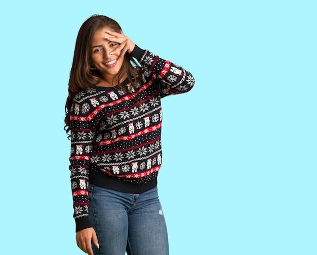 Volledige lichaams jonge vrouw die een kerstmisjersey draagt in verlegenheid bracht en tegelijkertijd lacht