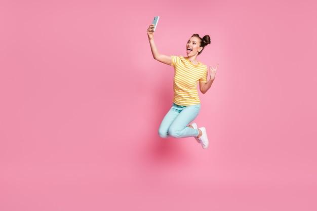Volledige lichaamsfoto van aantrekkelijke dame die telefoon vasthoudt en selfies maakt