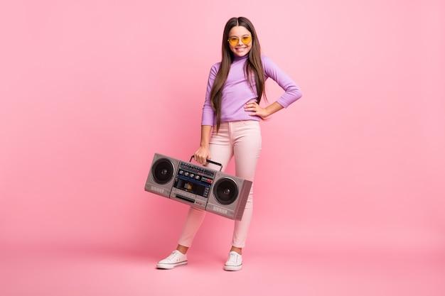 Volledige lichaamsfoto van een klein hipster-meisje dat een boomdoos vasthoudt en een paarse truibroek draagt die op een pastelkleurige achtergrond wordt geïsoleerd