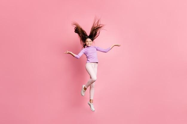 Volledige lichaamsfoto van een klein kind dat springt en een hand draagt, een paarse trui draagt, geïsoleerd op een pastelkleurige achtergrond