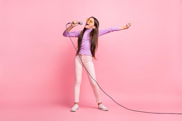 Volledige lichaamsfoto van een klein meisje dat een lied zingt op de microfoon, een paarse jumperbroek draagt, geïsoleerd op een pastelkleurige achtergrond