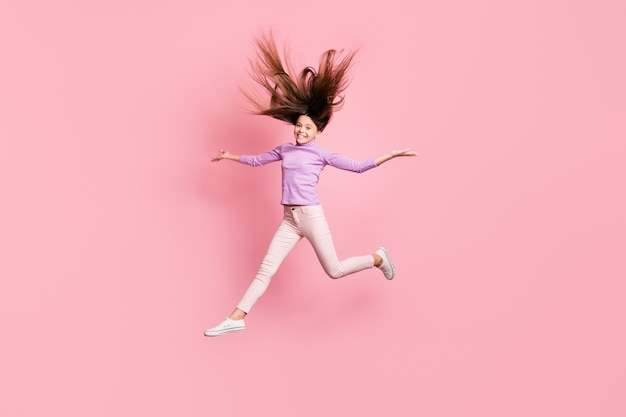 Volledige lichaamsfoto van een klein meisje dat springt, handen vasthoudt en een paarse trui draagt, geïsoleerd op een pastelkleurige achtergrond