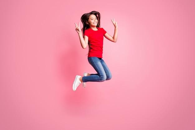 Volledige lichaamsfoto van een vrolijk kindmeisje dat springt en een v-teken draagt, een rode casual stijloutfit draagt, geïsoleerd op een pastelkleurige achtergrond