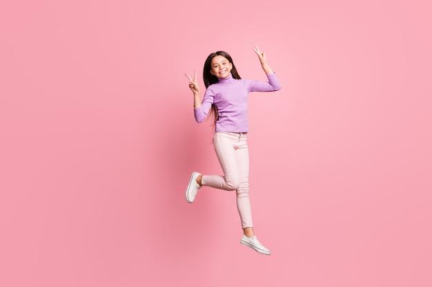 Volledige lichaamsfoto van een vrolijk klein meisje dat springt en een v-teken draagt, een violette trui draagt, geïsoleerd op een pastelkleurige achtergrond