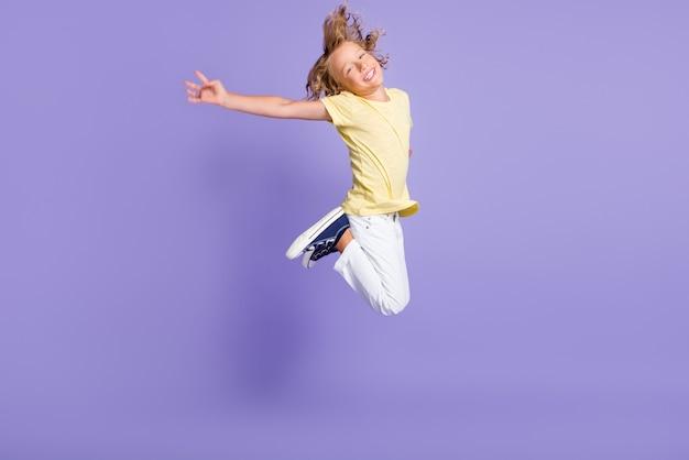 Volledige lichaamsfoto van een zorgeloze jongen die opspringt en kleding in casual stijl draagt, geïsoleerd over een violette kleurachtergrond