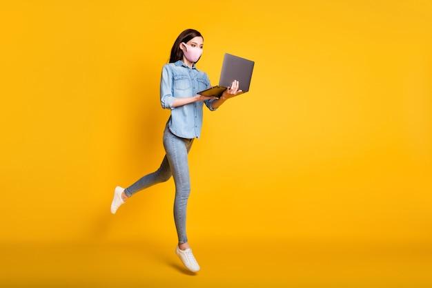 Volledige lichaamsfoto van geconcentreerde meid die op afstand werkt op afstand laptop
