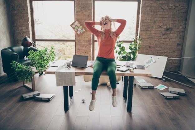 Volledige lichaamsfoto van gekke boze freelancer vrouw zit op tafel, hoor vreselijk nieuws over ontslag, voel een slecht humeur, raak blond haar aan, schreeuw schreeuwen in rommelige kantoor loft werkplek