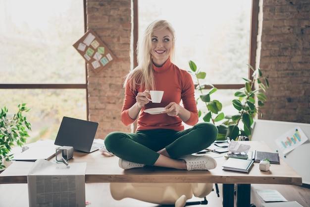 Volledige lichaamsfoto van gelukkige positieve vrouw bedrijfseigenaar zitten op tafel gekruiste benen rust ontspannen vasthouden koffiekopje drinken cappuccino dragen rode coltrui groene broek broek in rommelige kantoor loft