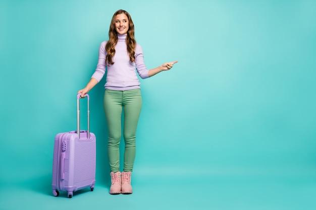 Volledige lichaamsfoto van grappige dame luchthaven met rollende reiskoffer directe vinger lege ruimte kies de beste luchtvaartmaatschappijen dragen lila trui groene broek schoeisel geïsoleerde pastel blauwgroen kleur
