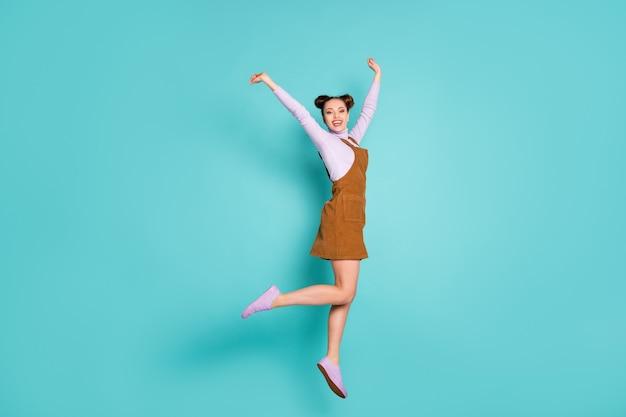 Volledige lichaamsfoto van opgewonden heerlijke gelukkige dame kampioen hoera sprong handen opsteken doorbraak gebaar draag twee broodjes paarse sneakers herfst trendy bruine mini jurk geïsoleerde groenblauw kleur achtergrond