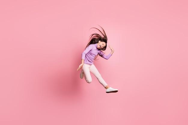 Volledige lichaamsfoto van opgewonden meisje dat springt, schreeuwt en haar kapsel vliegt geïsoleerd over pastelkleurige achtergrond