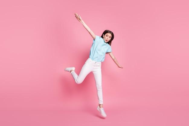 Volledige lichaamsfoto van verbaasd meisje dat hand in hand springt en witte gumshoes draagt, geïsoleerd over roze kleurachtergrond