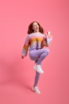 Volledige lichaamsfoto van vrij grappige roodharige dame die hoog opsteekt handen eerste plaats winnaar draagt casual trui leggins geïsoleerd over felroze kleur achtergrond mooie dame veel plezier