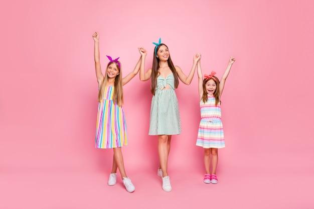 Volledige lichaamsfoto van vrolijke dames met hoofdbanden die handen opheffen die de heldere hoofdbanden van de rokkleding dragen die over roze achtergrond worden geïsoleerd