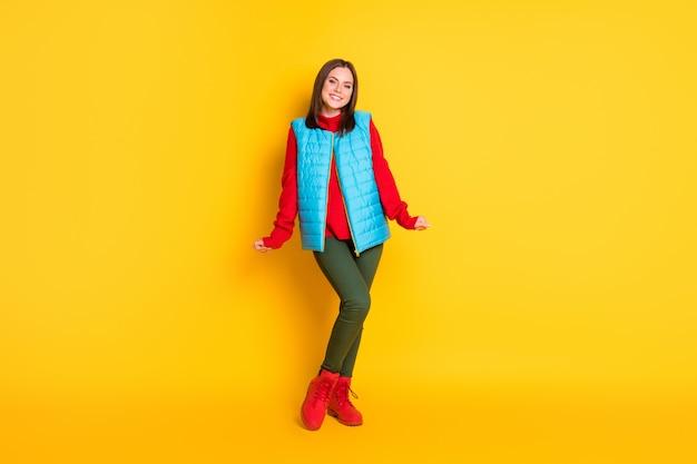 Volledige lichaamsgrootte foto van charmante mooie jonge dame vuisten mouwen stralend glimlachend meisjesachtig verlegen poseren draag groene broek blauw vest rode trui laarzen geïsoleerd felgele kleur achtergrond