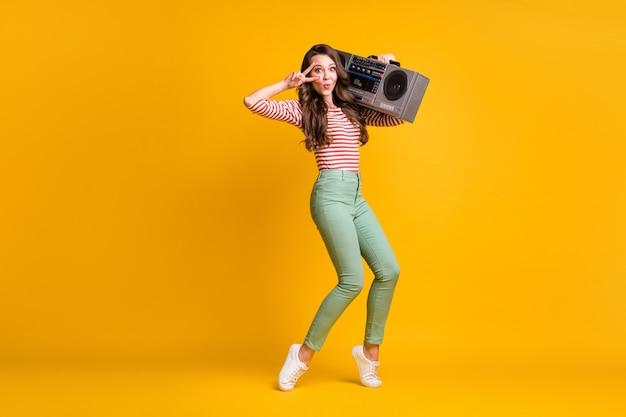 Volledige lichaamsgrootte foto van meisje luisteren naar retro boombox met v-teken dansen geïsoleerd op felgele kleur achtergrond
