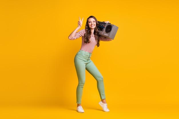 Volledige lichaamsgrootte foto van meisje luisteren naar retro boombox met v-teken gebaar geïsoleerd op levendige gele kleur achtergrond