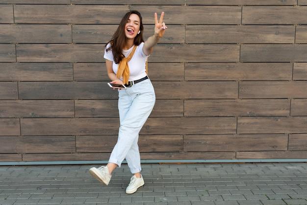Volledige lichaamsgrootte foto van mooie brunet jonge gelukkige vrouw die vrijetijdskleding draagt en luistert