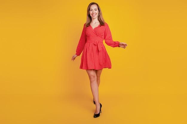 Volledige lichaamslengte van meisje loopt op gele achtergrond in mooie rode korte jurk met hoge hakken