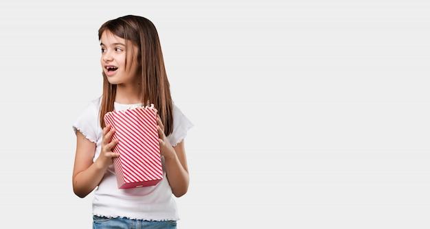 Volledige lichaamsmeisje gelukkig en gefascineerd, houdend een gestreepte popcornemmer