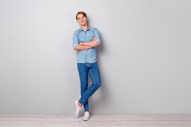 Volledige mannelijke smat werknemer man kruist zijn handen geïsoleerd over grijze kleur muur