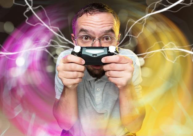 Volledige onderdompeling in gameplay jonge man met een videogamecontroller geïsoleerd op kleurrijk