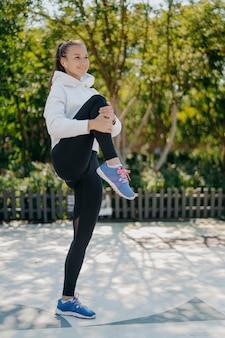 Volledige opname van actieve gezonde jonge vrouw die opwarmt voordat joggen in het park de knie omhoog houdt, sweatshirt-legging draagt en sneakers naar muziek luistert in oortelefoons. gezond levensstijlconcept.