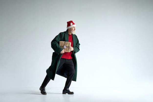 Volledige opname van een coole man van middelbare leeftijd met een kerstmuts die een casual outfit draagt ??