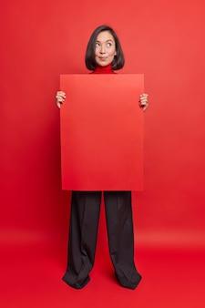 Volledige opname van een doordachte dromerige vrouw houdt een lege lege banner en denkt na over welke advertentie daar geplaatst wordt tegen een levendige rode muur
