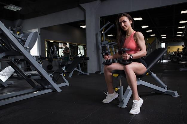 Volledige opname van een fitnessvrouw die traint met halters in een sportstudio, kopieer ruimte