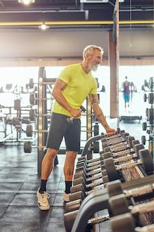 Volledige opname van een gelukkige atletische volwassen man in sportkleding die dumbbells neemt en in een grote kijkt