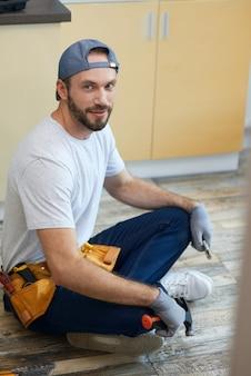Volledige opname van een jonge reparateur die naar een camera kijkt die loodgietersgereedschap in zijn handen houdt terwijl