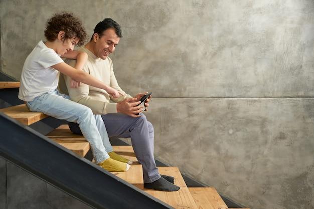 Volledige opname van een latijnse jongen die lacht terwijl hij samen met zijn vader op de trap zit, met behulp van digitale tablet-pc tijdens thuis studeren op afstand. quarantaine, thuisonderwijs, ouderschap. zijaanzicht