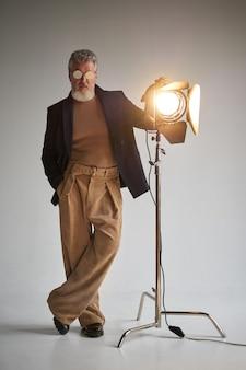 Volledige opname van een modieuze grijsharige man van middelbare leeftijd met een bril die naar de camera kijkt