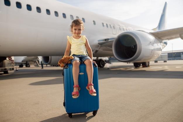Volledige opname van een schattig klein meisje dat haar speelgoed vasthoudt, naar de camera kijkt en op een koffer voor een groot vliegtuig zit. jeugd, reizen, vakantie concept