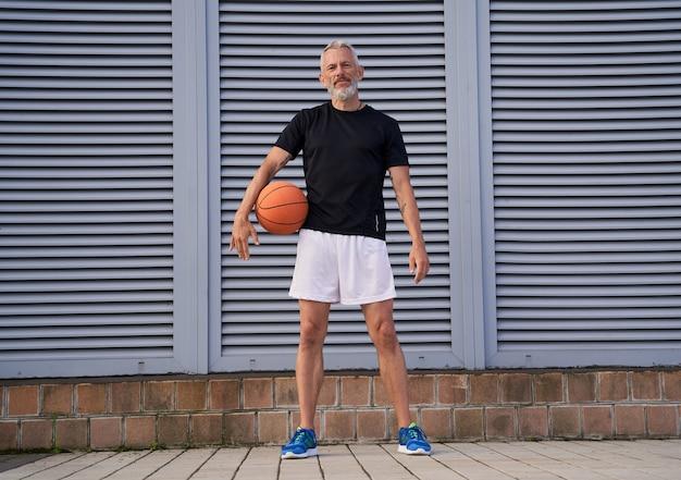 Volledige opname van een sportieve volwassen man in sportkleding die een basketbalbal vasthoudt en naar de camera kijkt