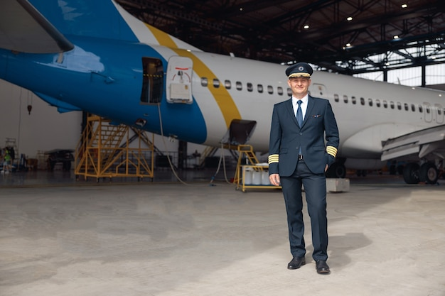 Volledige opname van een trotse piloot in uniform glimlachend naar de camera, staande voor een groot passagiersvliegtuig in de hangar van de luchthaven. vliegtuigen, beroep, transportconcept