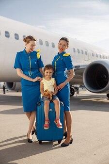 Volledige opname van lachende mooie stewardessen die in de buurt van schattig klein meisje staan, zittend op een koffer voor een groot vliegtuig en glimlachen naar de camera. jeugd, reizen, vakantie concept