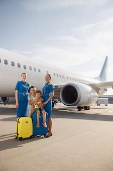 Volledige opname van mooie stewardessen die in de buurt van twee kinderen staan die op hun bagage voor een groot vliegtuig zitten en naar de camera glimlachen. familie, reizen, vakantie concept