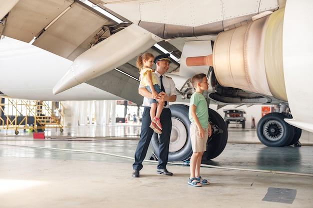 Volledige opname van piloot in uniform die delen van het vliegtuig en hun functies laat zien aan twee kleine kinderen die op excursie kwamen in de vliegtuighangar. beroep, kinderconcept