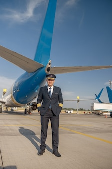 Volledige opname van professionele piloot in uniform die naar de camera kijkt, staande voor een groot passagiersvliegtuig klaar voor vertrek op de luchthaven. vliegtuigen, beroep, transportconcept