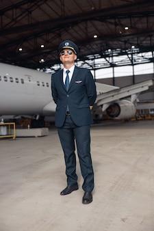 Volledige opname van trotse piloot in uniform en vliegenierszonnebril die wegglipt, staande voor een groot passagiersvliegtuig in de hangar van de luchthaven. vliegtuigen, beroep, transportconcept