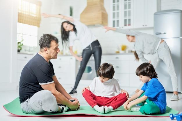 Volledige opname van twee kleine jongens die op een mat zitten met vader terwijl hun moeder en zus op de achtergrond trainen. actieve latijnse familie met ochtendtraining thuis
