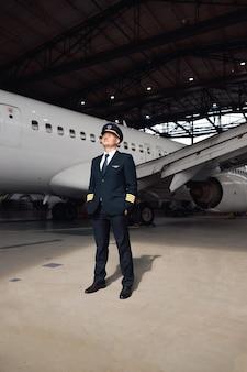 Volledige opname van zelfverzekerde piloot in uniform die wegkijkt, klaar voor de vlucht, staande voor een groot passagiersvliegtuig in de hangar van de luchthaven. vliegtuigen, beroep, transportconcept