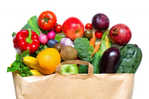 Volledige papieren zak met verschillende groenten en fruit op een witte achtergrond