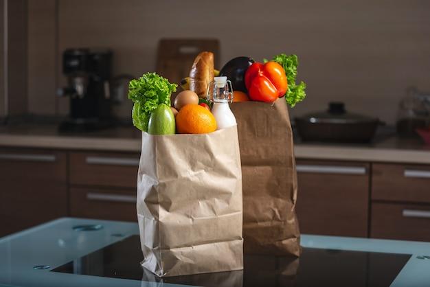 Volledige papieren zakken met voedsel op de keukentafel op donkere achtergrond