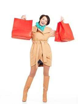 Volledige portret van gelukkige vrouw met boodschappentassen in herfst jas met groene sjaal staande geïsoleerd op wit
