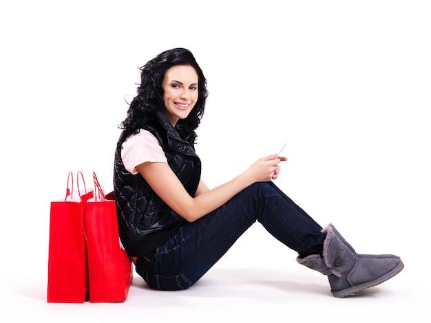 Volledige portret van glimlachende vrouw met rode boodschappentassen zittend op de vloer - geïsoleerd op wit.