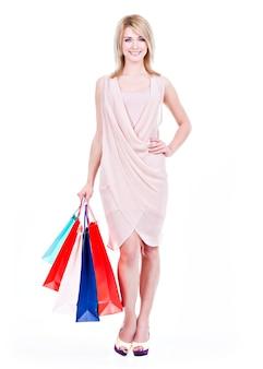 Volledige portret van lachende jonge blonde vrouw met kleurrijke boodschappentassen in roze jurk poseren op een witte achtergrond
